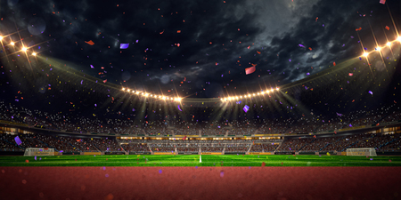 to field: Night stadium arena soccer field championship win. Confetti and tinsel Stock Photo