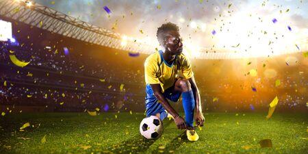 Black soccer player in action. Stadium field evening Standard-Bild