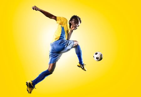 jugando futbol: futbolista negro en la acción de fondo amarillo