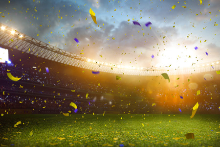 team victory: Evening stadium arena soccer field championship win. Confetti and tinsel . Yellow toning Stock Photo