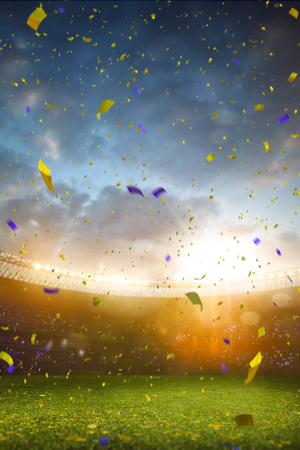 fans: Evening stadium arena soccer field championship win. Confetti and tinsel . Yellow toning Stock Photo