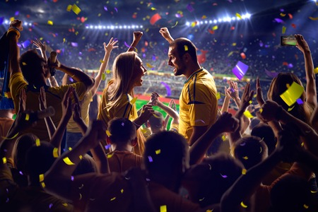 jugando futbol: Fans en el juego de f�tbol estadio Confeti y oropel