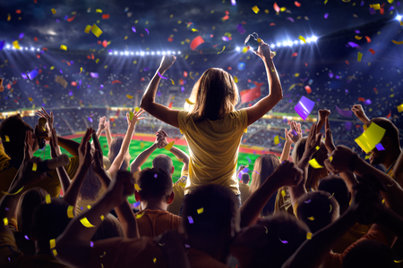 jugando futbol: Fans en el juego de fútbol estadio Confeti y oropel