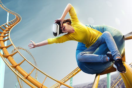 Jonge vrouw gebruikte virtual reality-helm Vr. Ze ziet een achtbaanpark Stockfoto