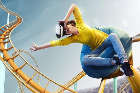 Mujer joven utilizó casco de realidad virtual Vr. Ella ve el parque de la montaña rusa Foto de archivo