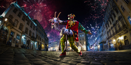 Night street circus performance whit clown, juggler. Festival city background. fireworks and Celebration atmosphere. Wide engle photo