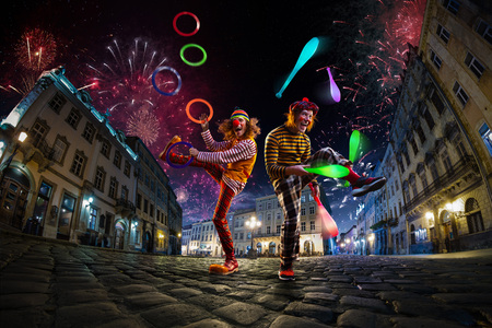 Night street circus performance whit two clowns, juggler. Festival city background. fireworks and Celebration atmosphere.
