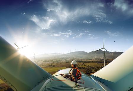 Glücklicher Ingenieur fühlt Erfolg nach guter Arbeit. Er steht auf einer Windmühle und sieht eine wunderschöne Sonnenuntergangslandschaft aus