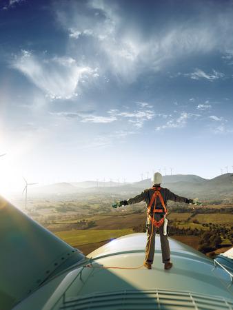 Glücklicher Ingenieur fühlt Erfolg nach guter Arbeit. Er steht auf einer Windmühle und sieht eine wunderschöne Sonnenuntergangslandschaft aus Standard-Bild