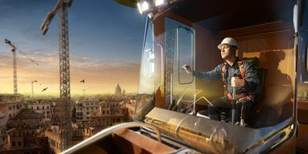 Ingenieur operator kraan in actie. Hij zit een top in kraancabine en is aan het werk. Rond prachtige zonsondergang Stockfoto