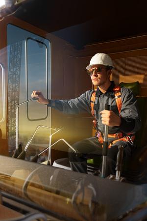 Inżynier operator dźwigu w akcji. Siedzi blatem w kabinie dźwigu i pracuje. Wokół pięknego zachodu słońca