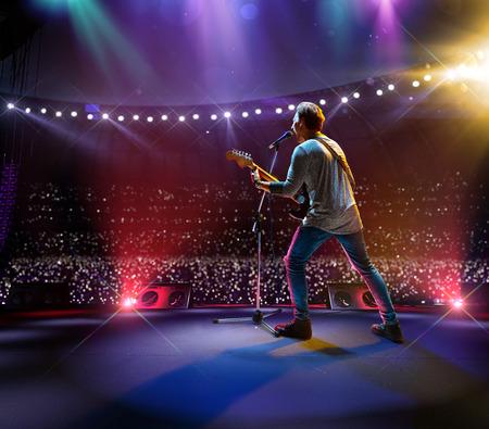 Célébrité rock star sur la scène principale du grand festival de musique. Autour d'un stade plein de spectateurs. les fans tiennent des lampes de poche Banque d'images