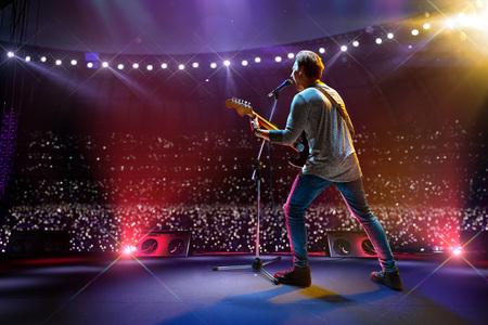 Rockster-beroemdheid op het grote muziekfestival van het hoofdpodium. Rond een vol stadion van toeschouwers. fans houden zaklampen vast Stockfoto