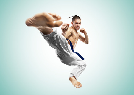 Karate fighter in action isolated gray background