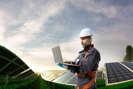Solar energy engineer using laptop for check station
