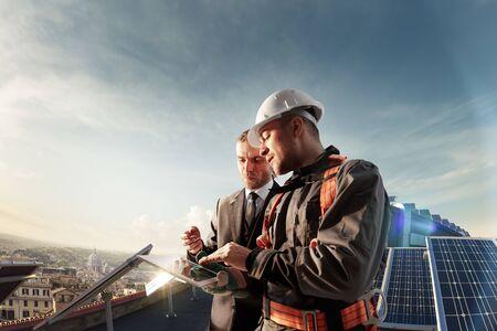 inżynier i biznesmen planujący nowy projekt ekologiczny. wokół panelu słonecznego i dachu