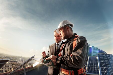 Ingenieur und Geschäftsmann, der ein neues Ökologieprojekt plant. rund um Solarpanel und Dach