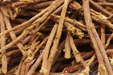 expectorant: Licorice root sticks lie on a wooden table