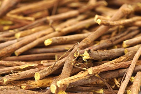 licorice: Licorice root sticks lie on a wooden table