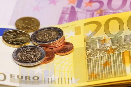 dinero falso: Varias monedas euro tendido en los billetes de banco euro