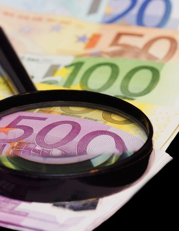 dinero falso: Euro banknotes are under a large magnifying glass Foto de archivo