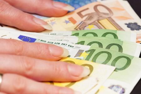 dinero falso: manos de la mujer hermosa que sostiene varios billetes en euros Foto de archivo