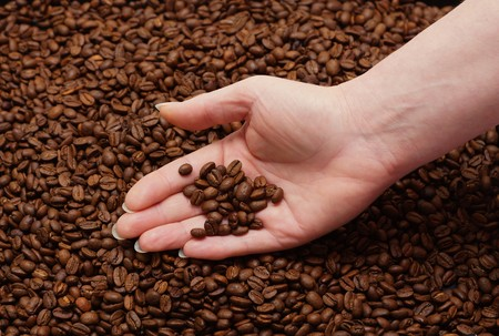 Woman hands and fresh coffee beans
