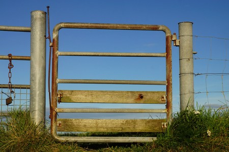 Metal gate on a dike under blue sky