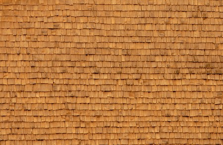 wood trade: Large wooden house wall of shingles in the evening sun