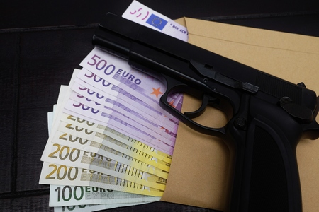 arms trade: Pistol is lying on a lot of euro banknotes
