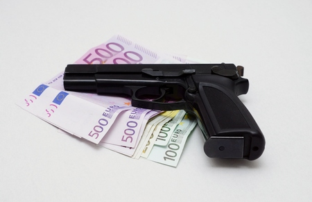 dinero falso: Pistol is lying on a lot of euro banknotes