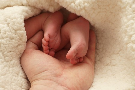 midwifery: Sweet baby feet in loving mother hand Stock Photo