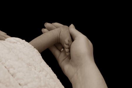 midwifery: Sweet baby foot in loving mother hand