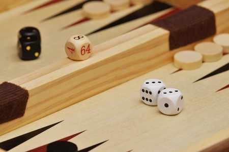 Cubes and game pieces on a backgammon board Stock Photo