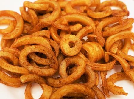 friso: Crujiente al horno curry fritas sobre un fondo blanco Foto de archivo
