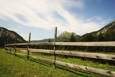 Wooden fence in the Tyrolean Alps under blue sky