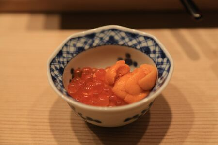Closeup of raw sea urchin and salmon roe serve in small bowl