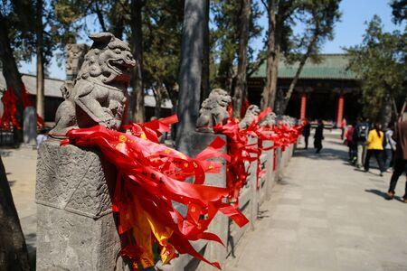 ライオン像サラウンドに中国の寺院の中の赤いリボンで飾られた石造りの塀