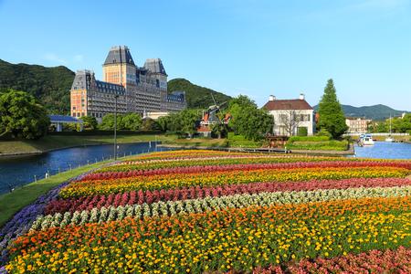 Jardim de flores coloridas perto do rio em Huis ten bosch em Nagasaki, Japão Foto de archivo - 92743625