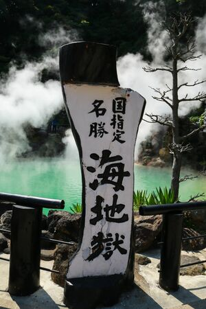 Greenish blue hot spring called Umi Jigoku, sea hell, and its name banner in Beppu, Oita, Japan                                           Japanese word translated as : Scenic spot, Umi Jigoku