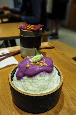 Closeup of sweet potato bingsu; Korean ice shavings dessert, with small white flower decorated