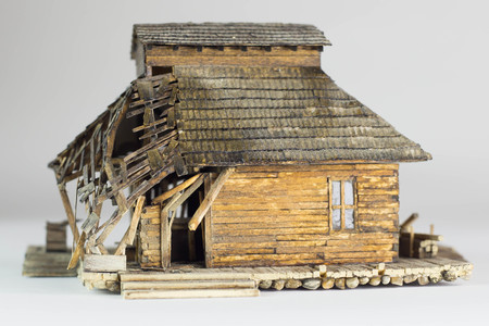 Western ghost town railway station made of matchsticks, back view, broken roof