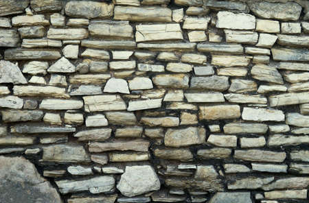 weatherworn: fragment of old wall made of irregular shaped stones Stock Photo