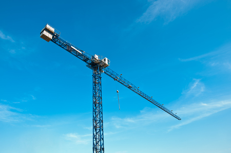 steel tower: Tower crane over blue sky, lit by early afternoon sunlight. Stock Photo