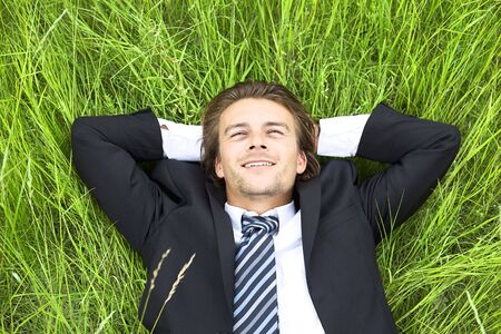 Well-dressed young businessman is resting in a field photo