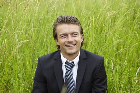 Smiling young businessman is sitting in a field photo
