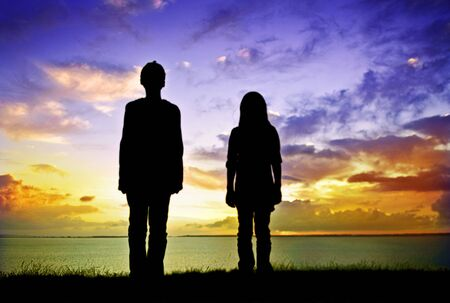 boy and girl looking at an sunset Stock Photo