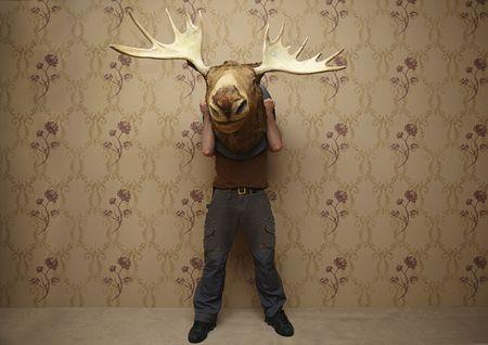 man is hiding behinde a moose head