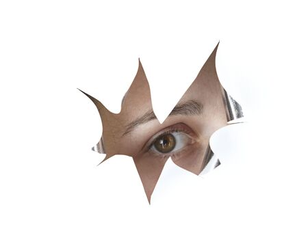 an eye peeking through a hole in the paper Stock Photo - 5424842