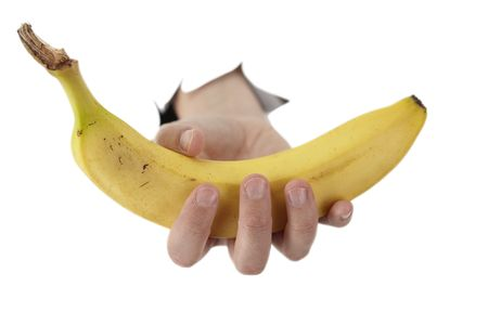 a hand from a hole is holding a banana